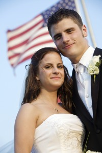 Bride and grrom standing in front of american flag.