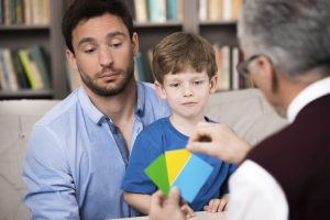 Little boy and his father talking with psychologist. Psychologist making test with boy. There are many books in psychologist office